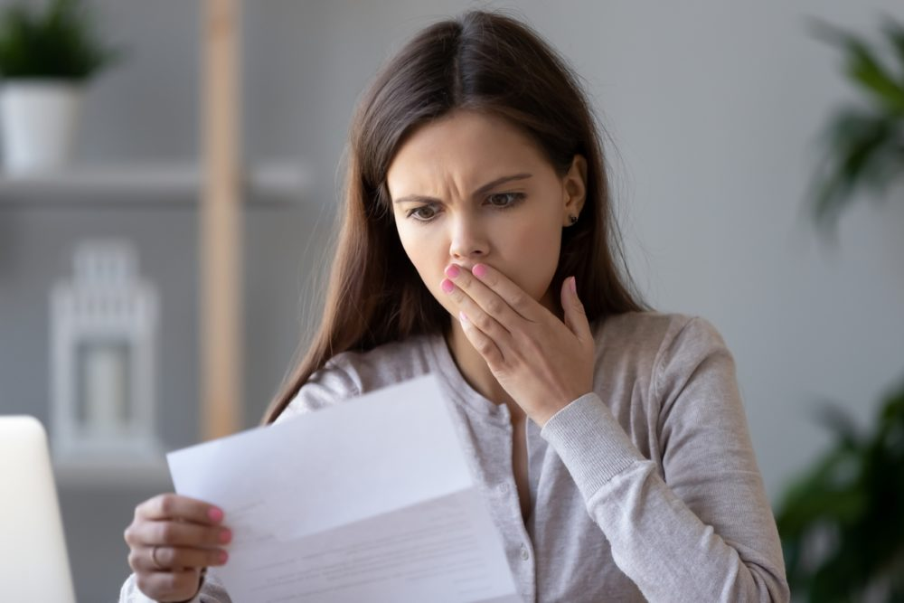 Stressed young taxpayer reads IRS letter